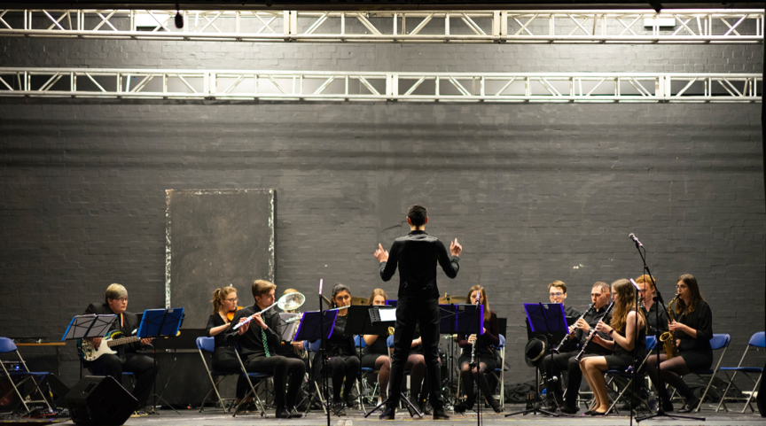 An orchestra playing with a conductor